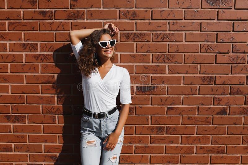 Mulher nova encantador feliz do moderno com um sorriso bonito, com cabelo encaracolado fotografia de stock royalty free