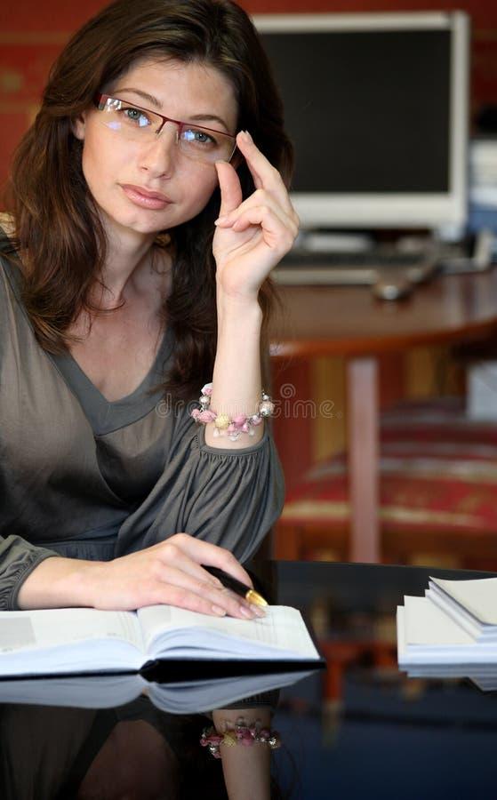 Mulher nova entre livros foto de stock
