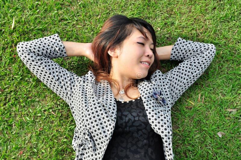 A mulher nova está descansando em um campo verde fotografia de stock royalty free