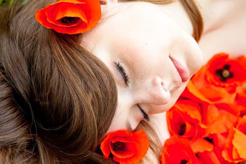 A mulher nova está dormindo - face em flores vermelhas fotos de stock royalty free