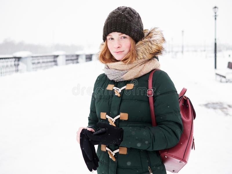 Mulher nova feliz adorável do ruivo no chapéu verde do Parka que tem o divertimento no cais de exploração do rio do inverno nevad imagem de stock royalty free