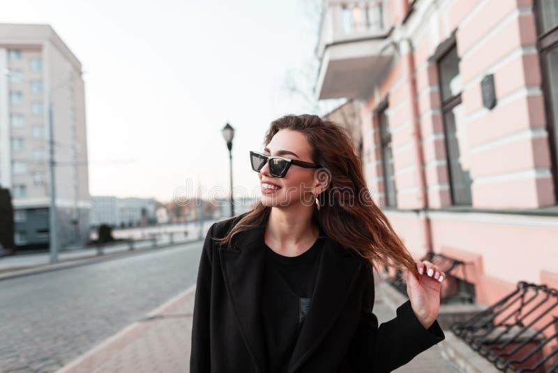 A mulher nova feliz atrativa engraçada do moderno com um sorriso positivo em um revestimento preto elegante em óculos de sol escu imagens de stock