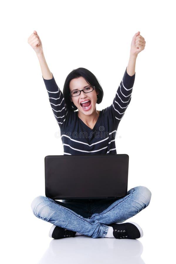 Mulher nova feliz com os punhos que usam acima seu portátil imagem de stock royalty free