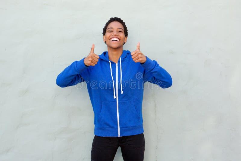 Mulher nova feliz com polegares acima fotografia de stock royalty free