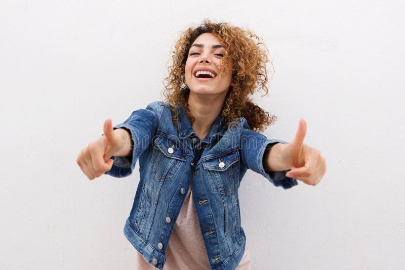 Mulher nova feliz com polegares acima foto de stock royalty free