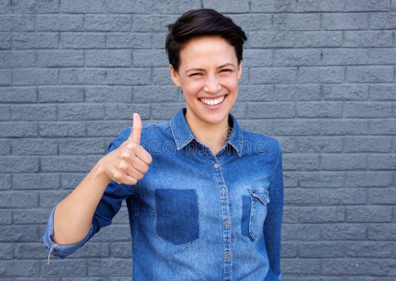 A mulher nova feliz com polegares levanta o sinal fotos de stock royalty free