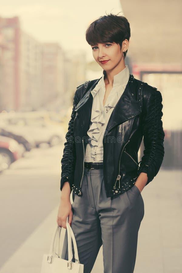 Mulher nova feliz da forma no casaco de cabedal com bolsa imagens de stock royalty free
