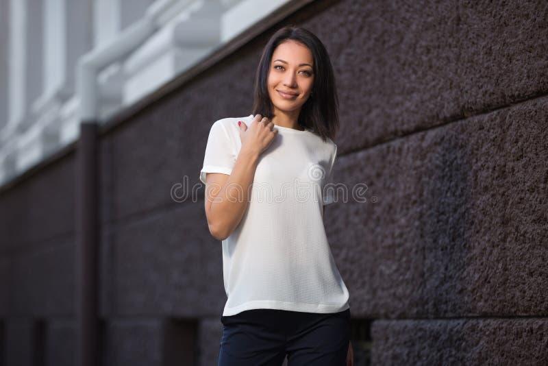 Mulher nova feliz da forma no t-shirt branco na rua da cidade foto de stock