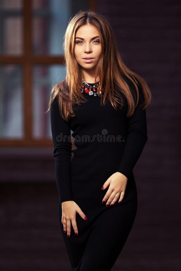 Mulher nova feliz da forma no vestido preto na rua da noite imagem de stock royalty free