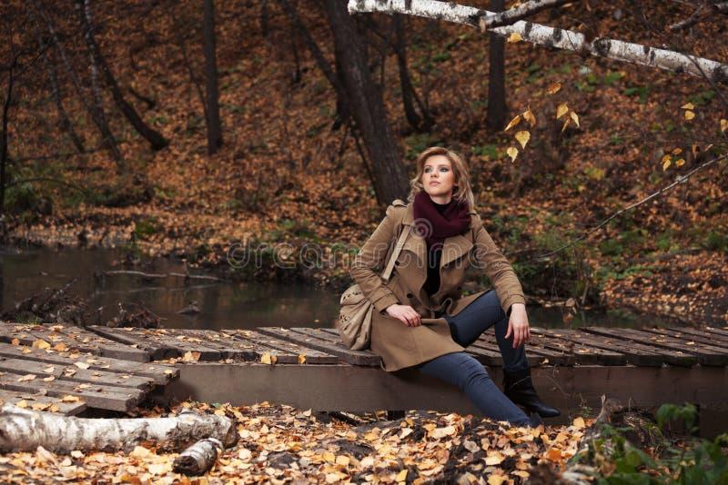 Mulher nova feliz da forma que senta-se na ponte de madeira no parque do outono imagens de stock royalty free