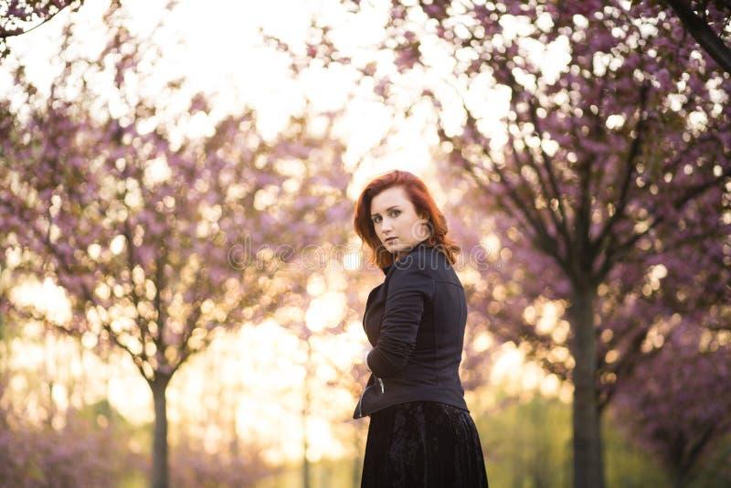 Mulher nova feliz do dançarino do curso que aprecia o tempo livre em um parque da flor de cerejeira de sakura - menina branca cau imagens de stock