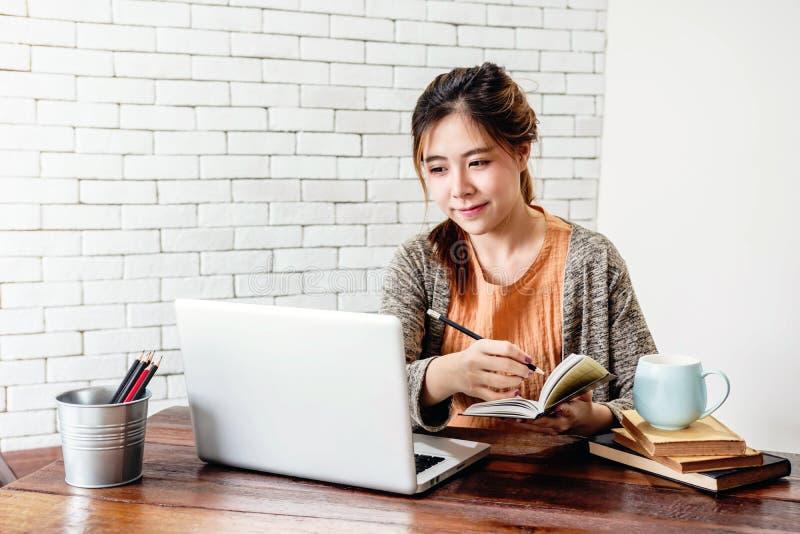 Mulher nova feliz do Freelancer que trabalha no portátil do computador em acolhedor foto de stock