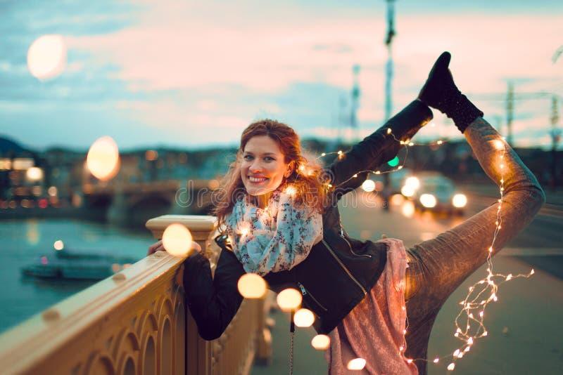 Mulher nova feliz do ruivo que faz a ioga com luzes feericamente fora imagem de stock