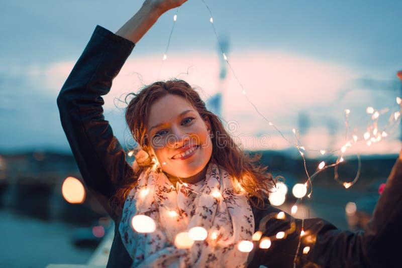 Mulher nova feliz do ruivo que joga com luzes feericamente fora e foto de stock royalty free