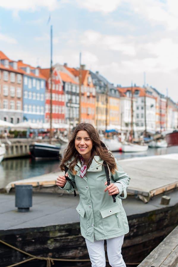 Mulher nova feliz do turista com a trouxa em Copenhaga fotografia de stock