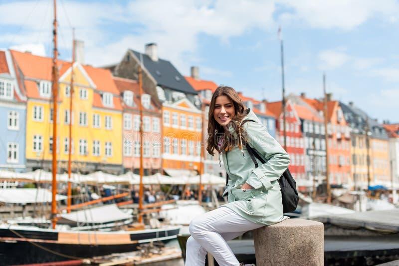 Mulher nova feliz do turista com a trouxa em Copenhaga imagem de stock royalty free