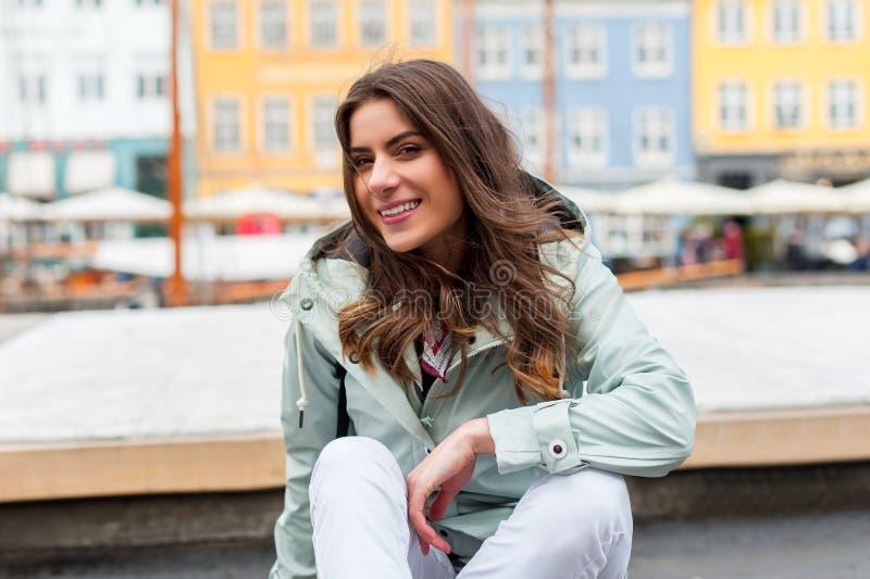 Mulher nova feliz do turista com a trouxa em Copenhaga imagens de stock