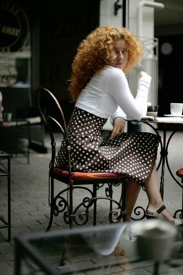 Mulher nova feliz em um café da rua do estilo de Paris imagens de stock royalty free