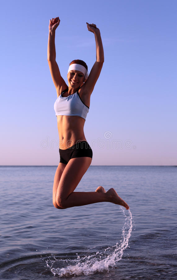 A mulher nova feliz está saltando fotografia de stock royalty free