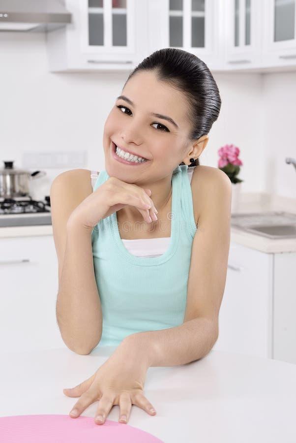 Mulher nova feliz na cozinha fotos de stock