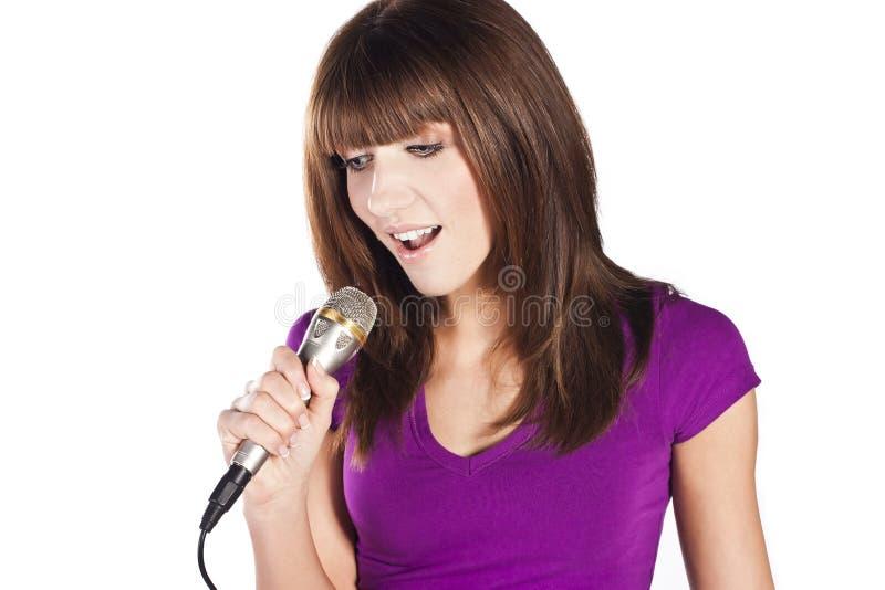 Mulher nova feliz que canta com microfone fotografia de stock