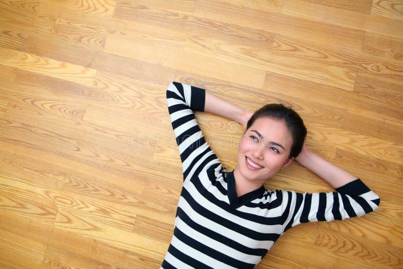 Mulher nova feliz que encontra-se no assoalho de madeira que olha acima foto de stock