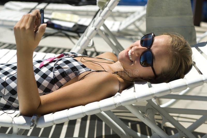 Mulher nova feliz que escuta a música no Sun foto de stock