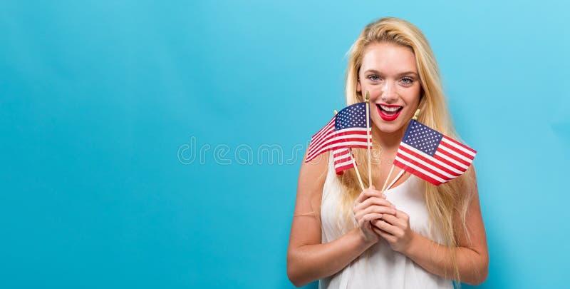 Mulher nova feliz que prende uma bandeira americana imagem de stock