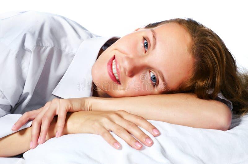 Mulher nova feliz que relaxa na cama foto de stock
