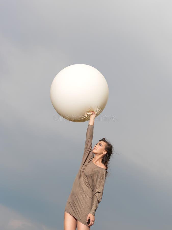 Mulher nova feliz que salta com balão imagens de stock royalty free