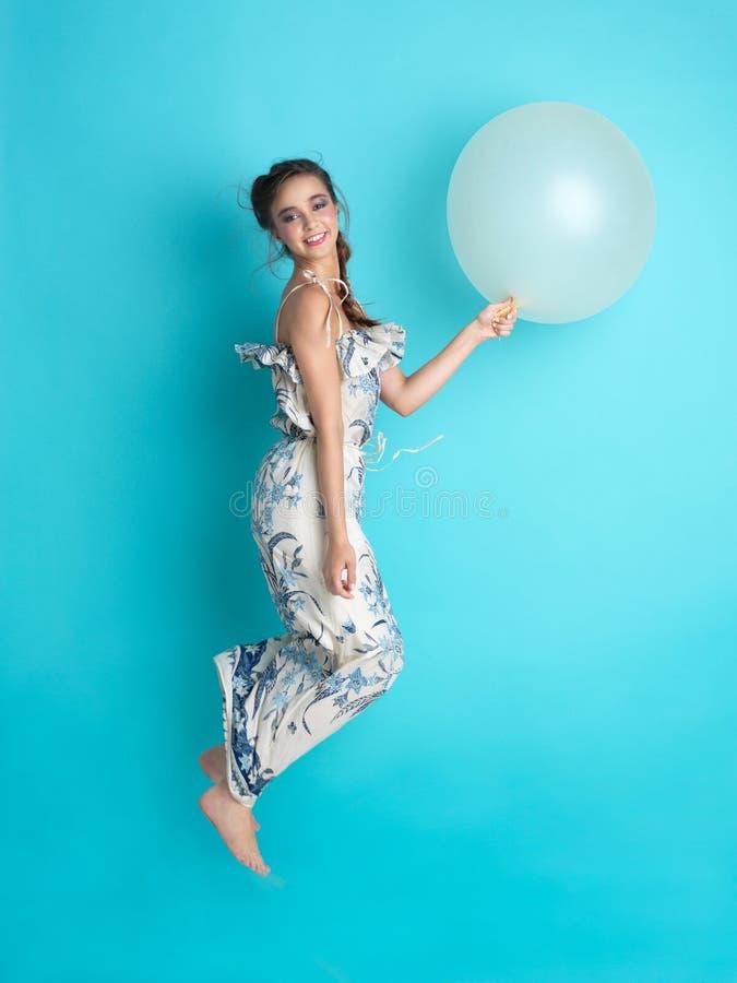 Mulher nova feliz que salta com balão fotografia de stock