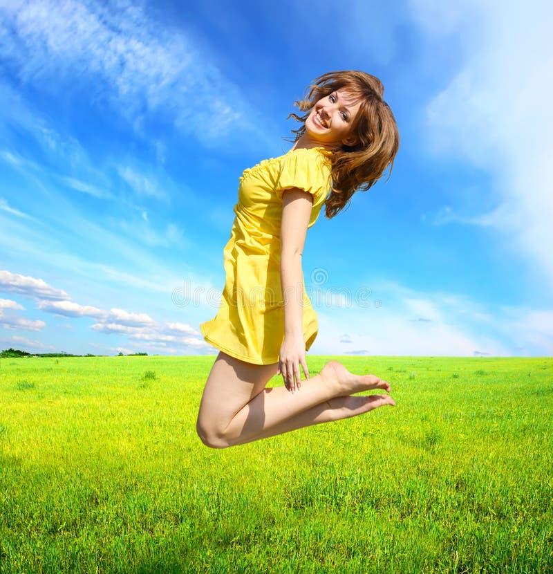 Mulher nova feliz que salta em um campo fotografia de stock