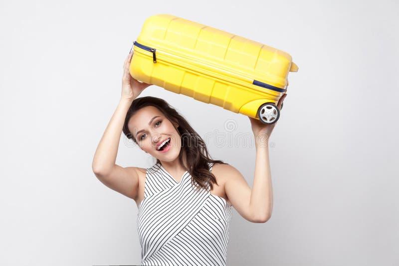 Mulher nova forte engraçada do viajante em posição listrada do vestido e imagens de stock royalty free