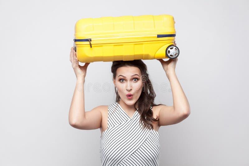 Mulher nova forte engraçada do viajante em posição listrada do vestido e fotografia de stock