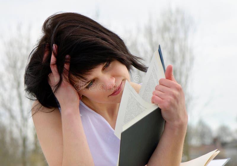 A mulher nova lê o livro fotos de stock