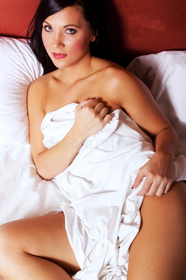 Mulher nova lindo que descansa na cama imagens de stock