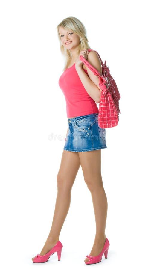 Mulher nova loura no vermelho com saco vermelho foto de stock
