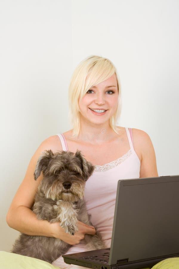 Mulher nova na cama com o cão do portátil e do schnauzer fotografia de stock royalty free