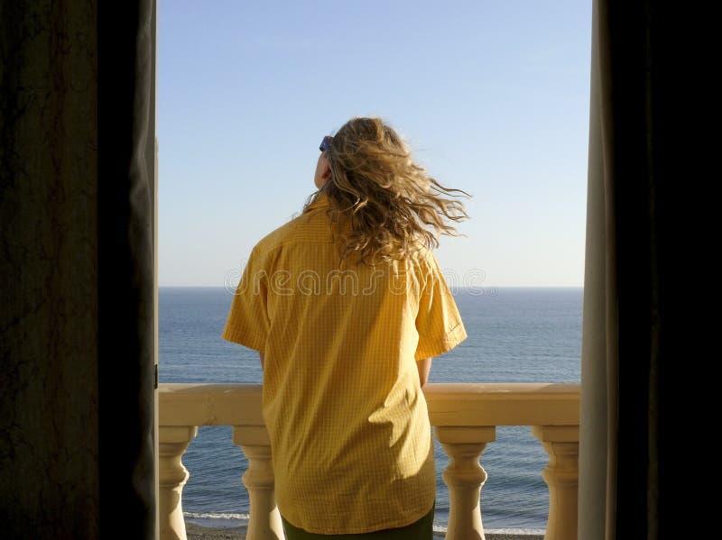 Mulher nova na camisa dos homens que olha o mar fotografia de stock royalty free