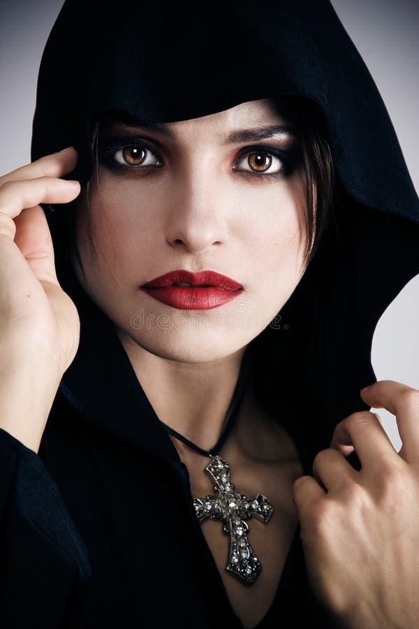 Mulher nova na capa preta com cruz fotos de stock