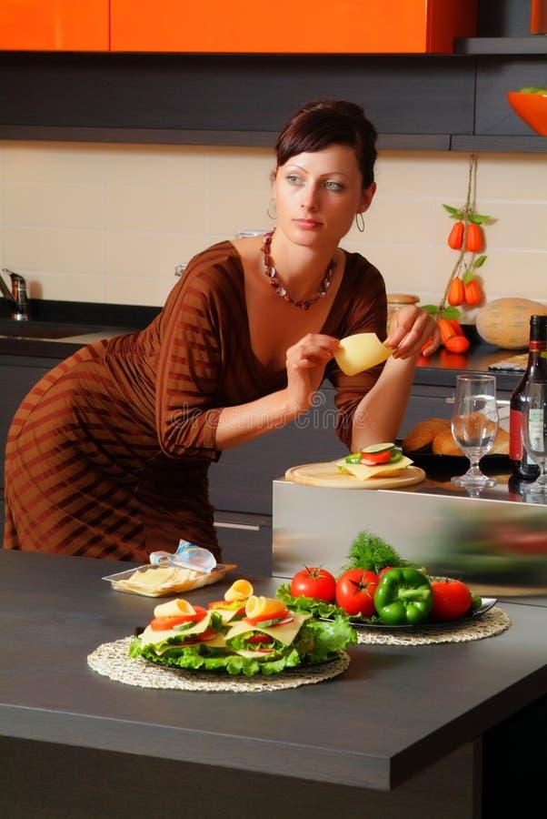 A mulher nova na cozinha fotografia de stock royalty free