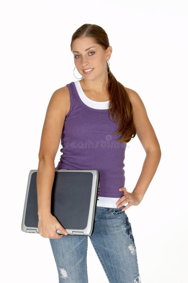 Mulher nova na parte superior de tanque roxa com o portátil sob o braço foto de stock