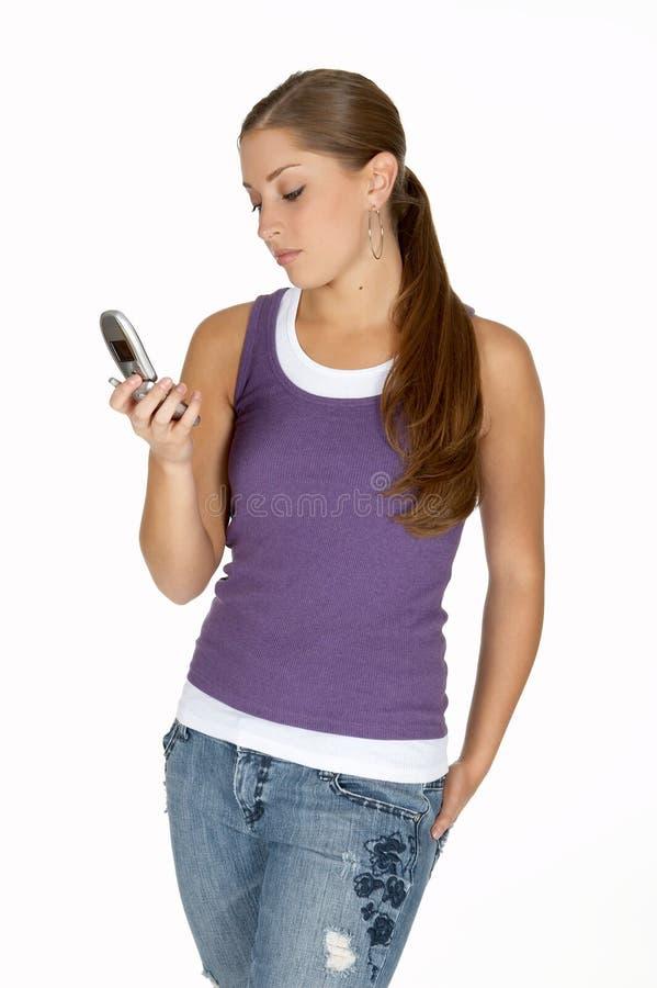 Mulher nova na parte superior de tanque roxa que olha o telefone de pilha imagem de stock