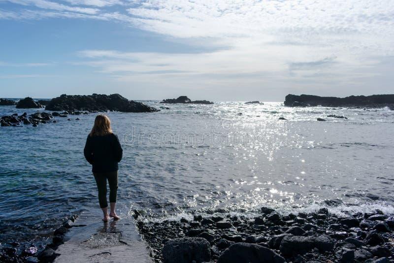 Mulher nova na praia Est? jogando com ?gua fotos de stock royalty free