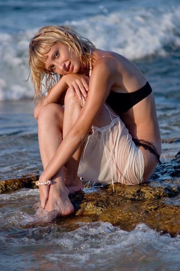 Mulher nova na praia na água foto de stock royalty free