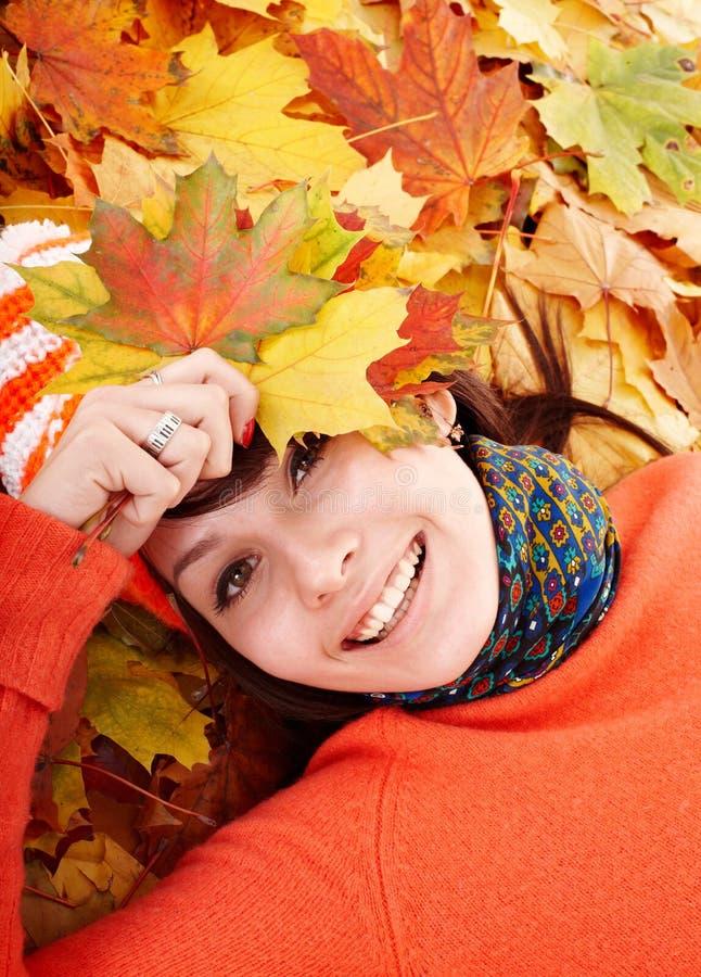 Mulher nova nas folhas alaranjadas do outono. fotografia de stock