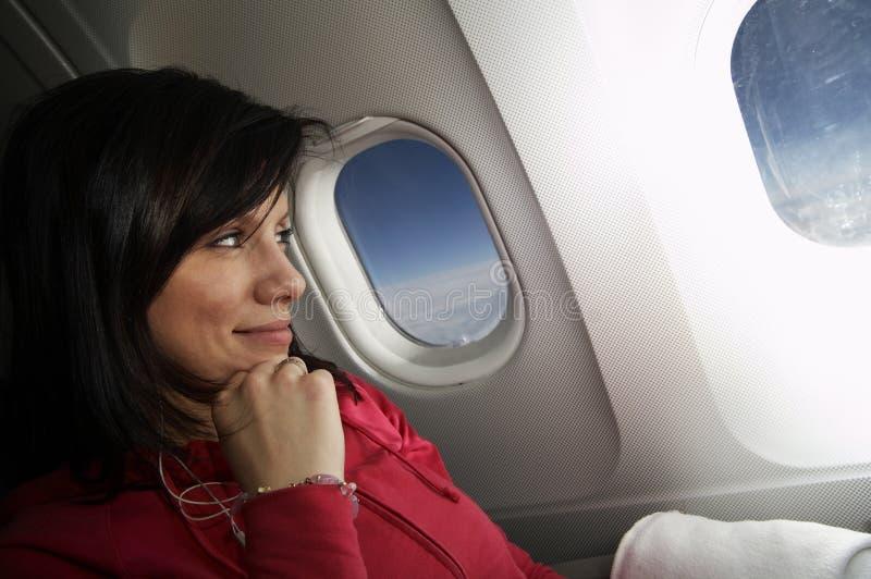 Mulher nova no avião fotos de stock