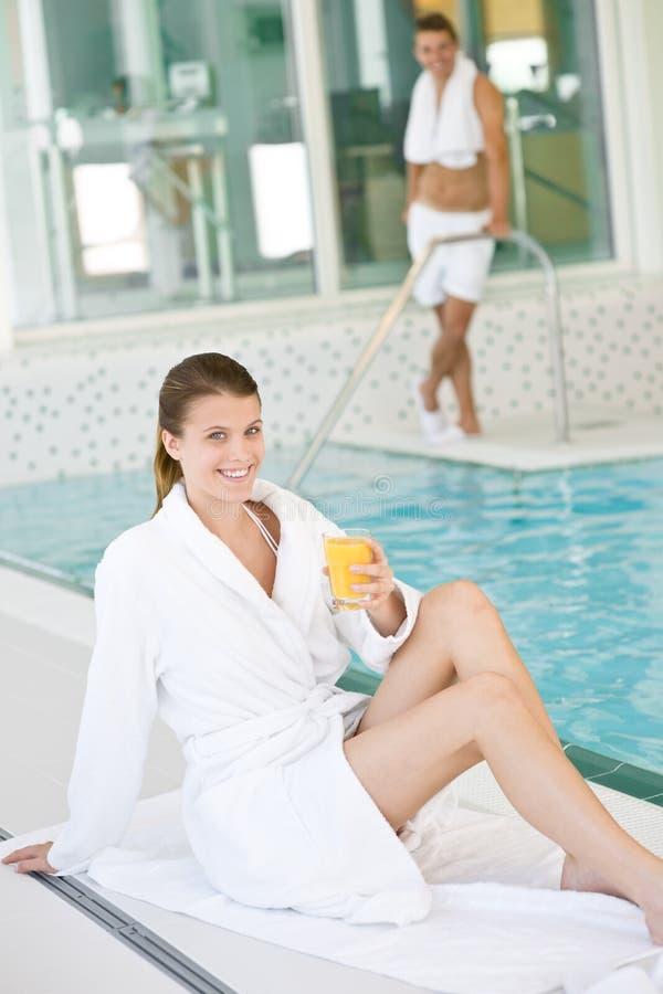 A mulher nova no bathrobe relaxa na piscina foto de stock