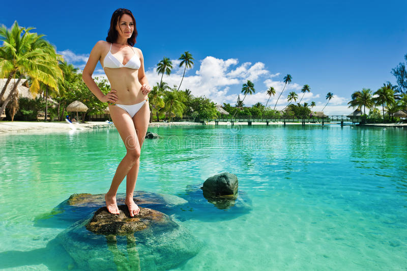 Mulher nova no biquini branco que está na praia fotografia de stock royalty free