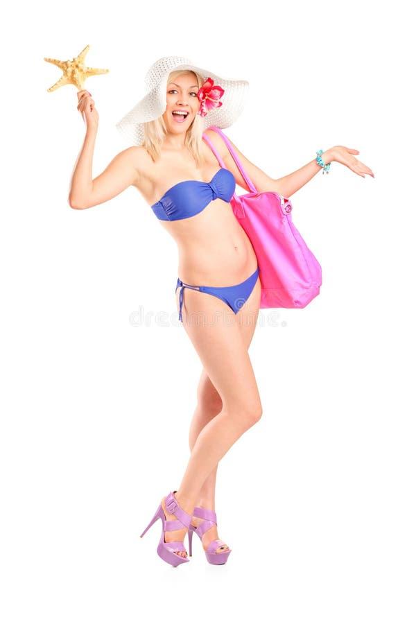 Mulher nova no biquini que prende uns starfish e um saco foto de stock